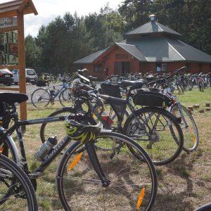 Rowery stojące na trawie, w głębi drewniany budynek ze spadzistym dachem i drewniane tablice edukacyjne