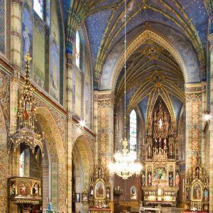 Wnętrze bogato zdobionego kościoła. Na ścianach i suficie kolorowa polichromia. W centralnym punkcie ołtarz.